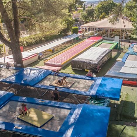 Les filles, après un entraînement gym du Summer Camp Pertuis, se rassemblent en cercle  pour une photo de groupe  sur le trampoline fosse de la salle.